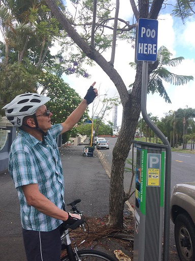 Footbiker Pointing to Parking Sign